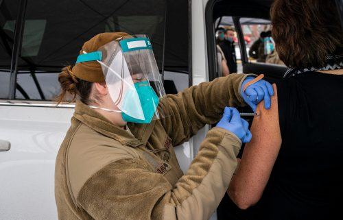 Washington National Guard medic Caityln Smith administers a COVID-19 vaccine to a patient at Town Toyota Center on January 26 in Wenatchee