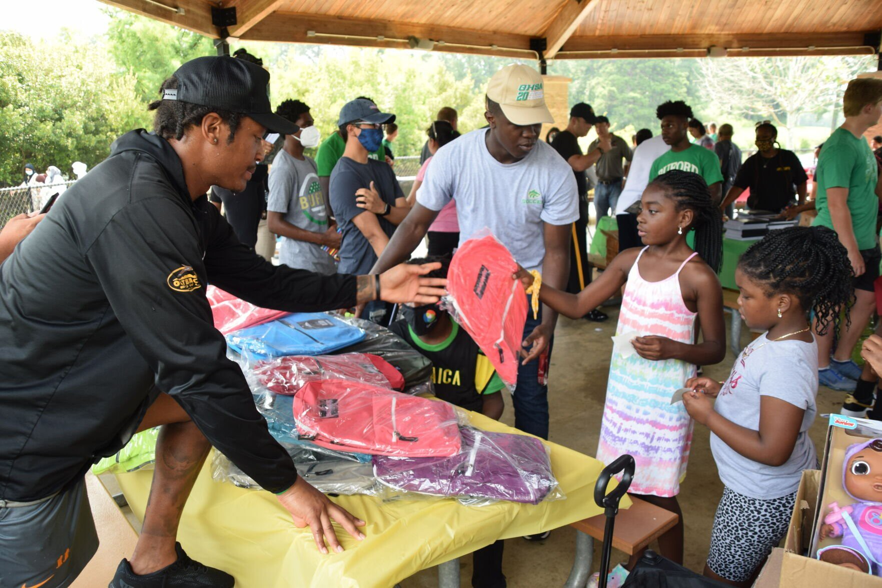 <i>Curt Yeomans/Gwinnett Daily Post</i><br/>Volunteers hand a backpack to a child at the Gwinnett County Sheriff's Office back to school celebration.