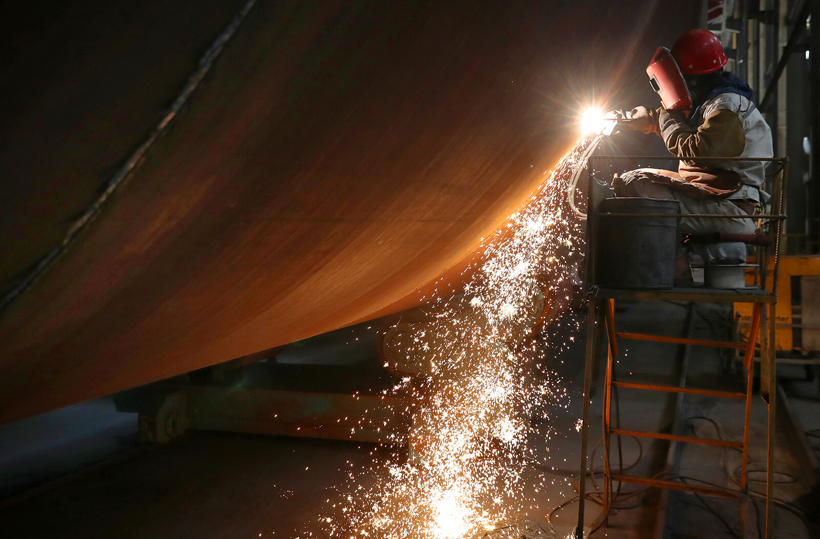 <i>Xu Congjun/FeatureChina/Getty Images</i><br/>A welder works at a factory of wind farm facilities in Rudong county in east China's Jiangsu province on June 7. China is releasing its latest quarterly economic growth figures on July 15