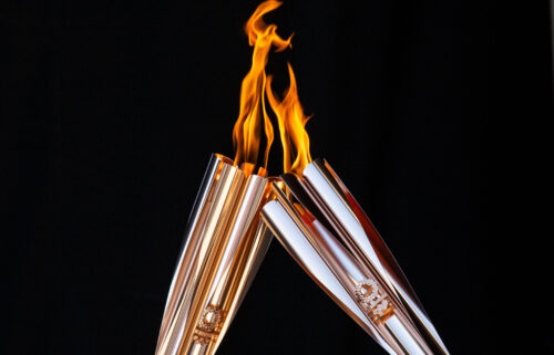 Torch bearers exchange the flame during the Olympic Torch Relay Celebration event on July 21