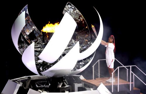 Naomi Osaka of Team Japan lights the Olympic cauldron with the Olympic torch during the Opening Ceremony of the games.