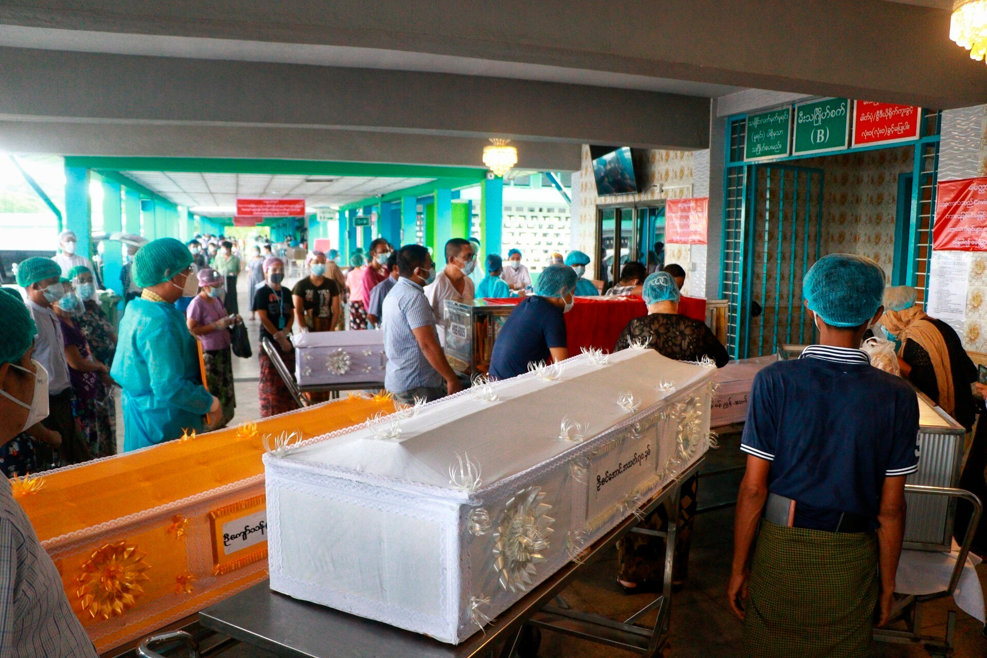 <i>AP</i><br/>People wearing face masks wait while caskets with bodies are queued outside a crematorium at the Yay Way cemetery in Yangon