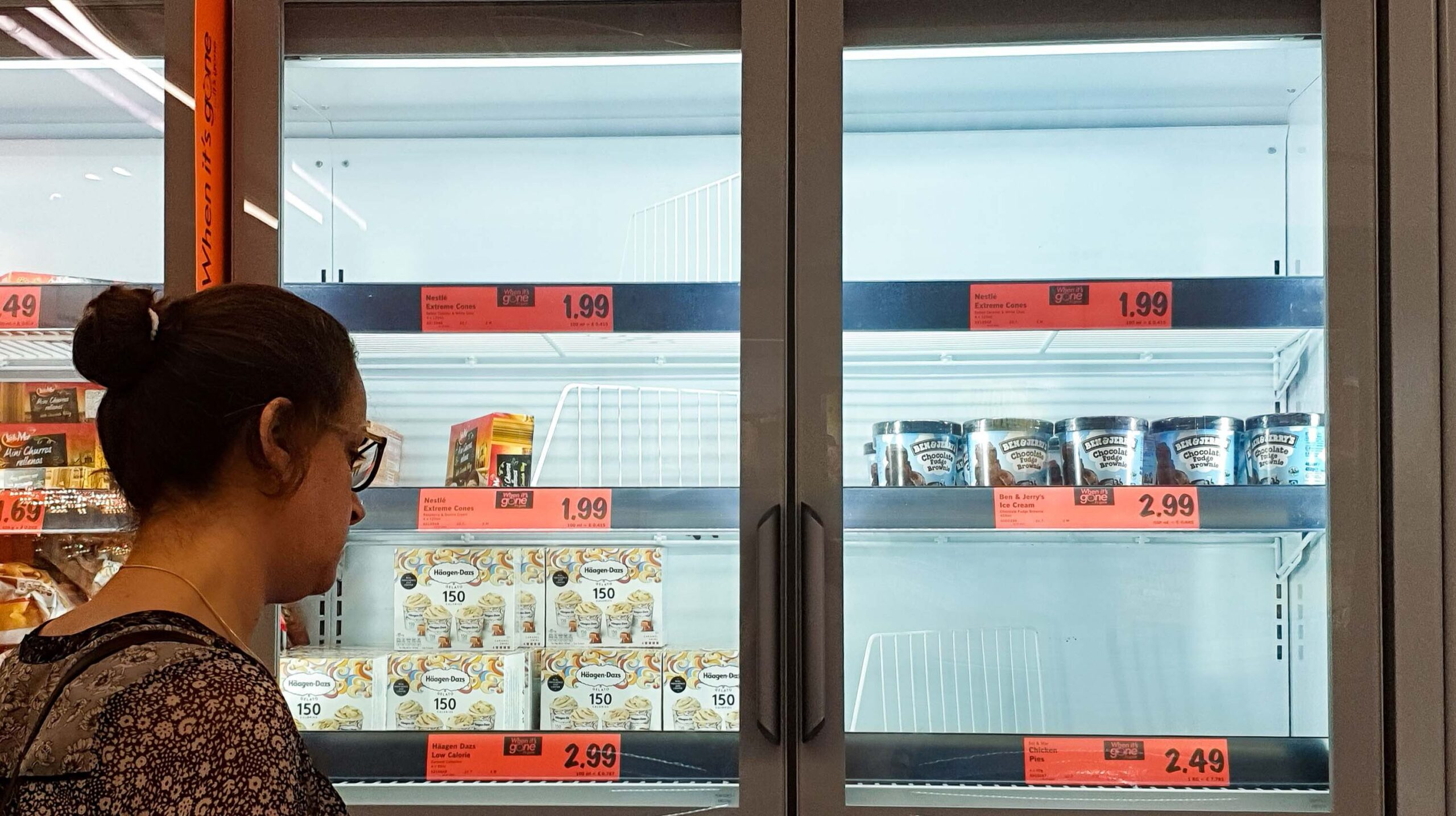 <i>Dinendra Haria/LNP/Shutterstock</i><br/>A customer looks at the depleted stock of ice cream at a Lidl supermarket. A dramatic surge in Covid-19 cases is forcing hundreds of thousands of workers to stay home in Britain