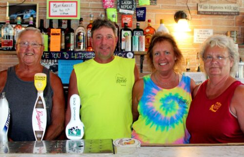 The last two sets of owners of Leipsic Tavern pose behind the bar: Danny Schmitt