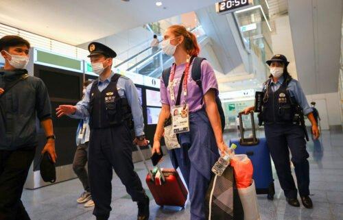 Kristina Timanovskaya is escorted by police officers at Haneda international airport in Tokyo