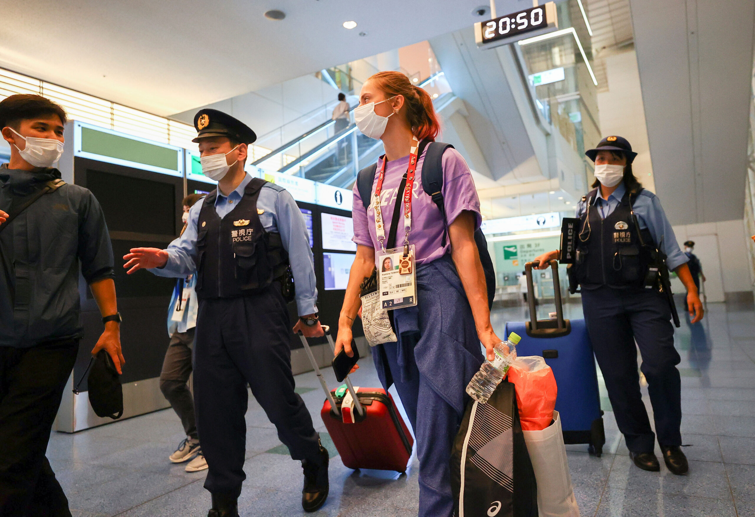 <i>Issei Kato/Reuters</i><br/>Kristina Timanovskaya is escorted by police officers at Haneda international airport in Tokyo