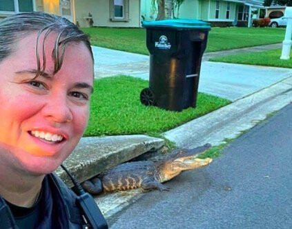 <i>Palm Bay Police/Facebook</i><br/>A Palm Bay police officer took a selfie with an alligator emerging from a storm drain.