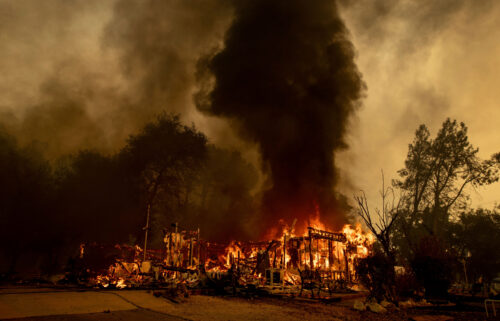 Flames consume a house as the Fawn Fire burns north of Redding on September 23.