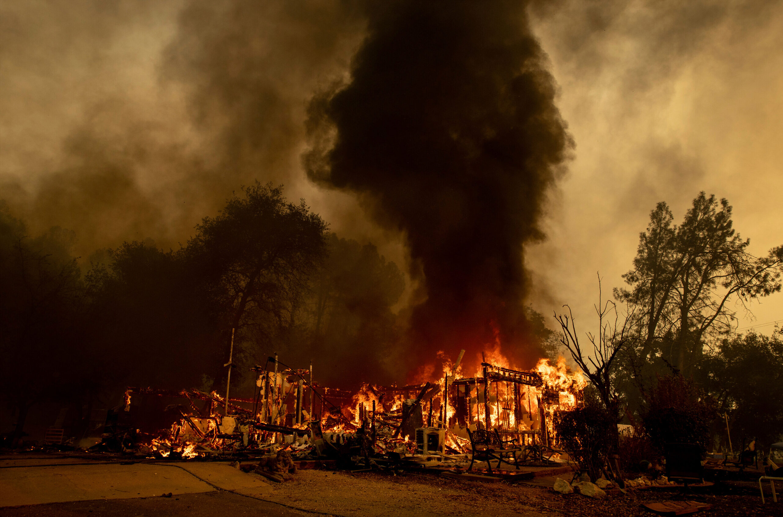 <i>Ethan Swope/AP</i><br/>Flames consume a house as the Fawn Fire burns north of Redding on September 23.