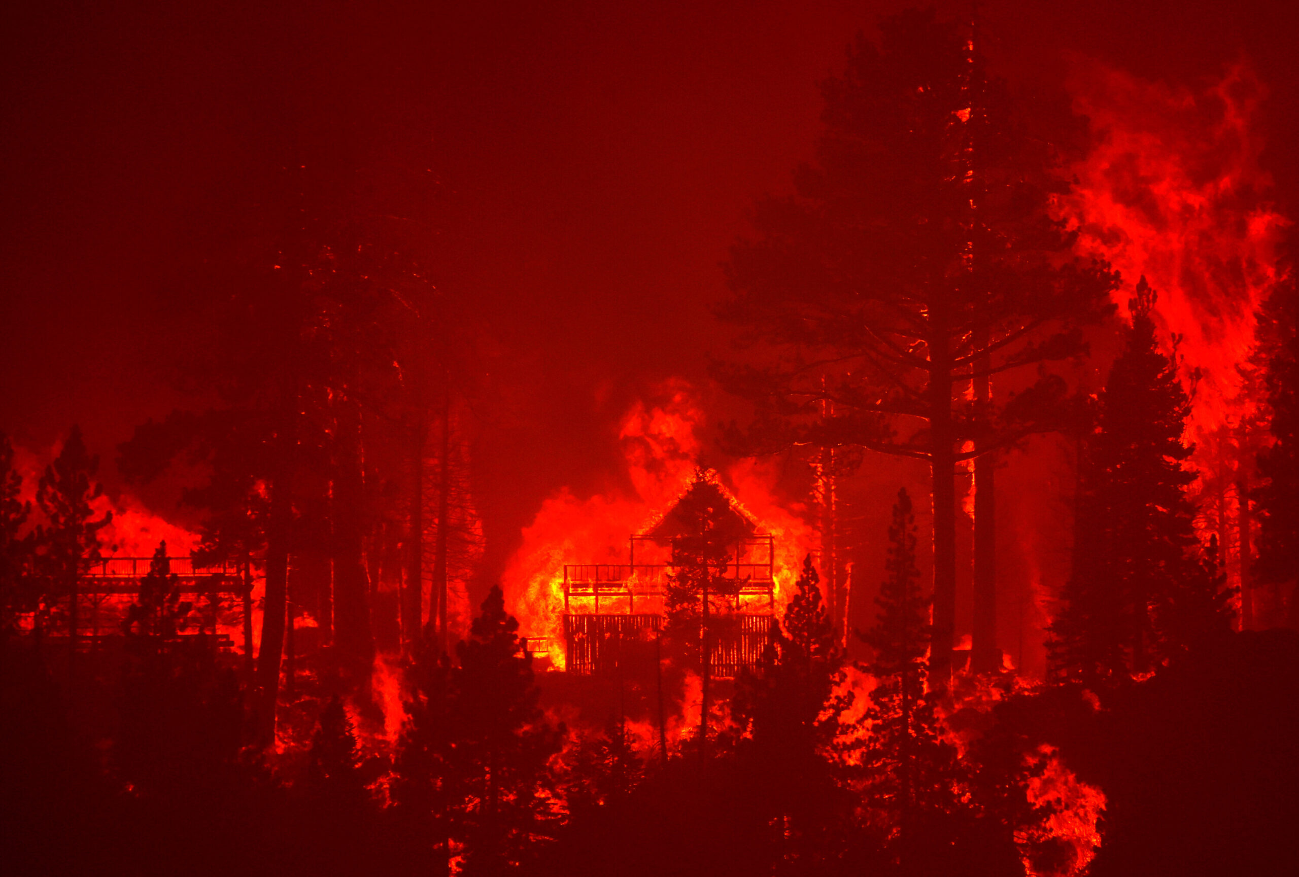 <i>Justin Sullivan/Getty Images</i><br/>The Caldor Fire burns homes near South Lake Tahoe