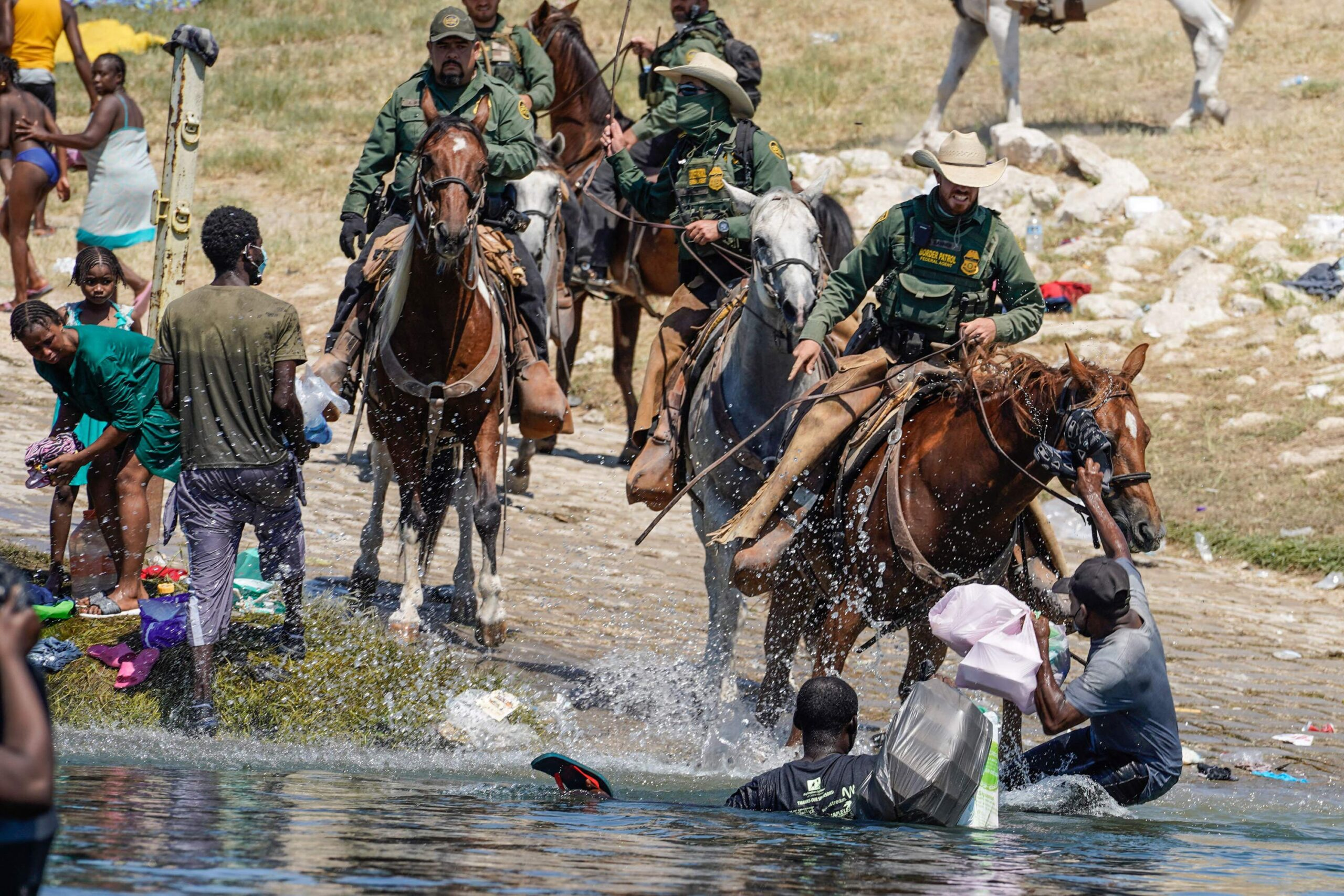 <i>Paul Ratje/AFP/Getty Images</i><br/>US Border Patrol agents on horseback try to stop Haitian migrants on Sunday from entering an encampment on the banks of the Rio Grande near the Acuna Del Rio International Bridge in Del Rio