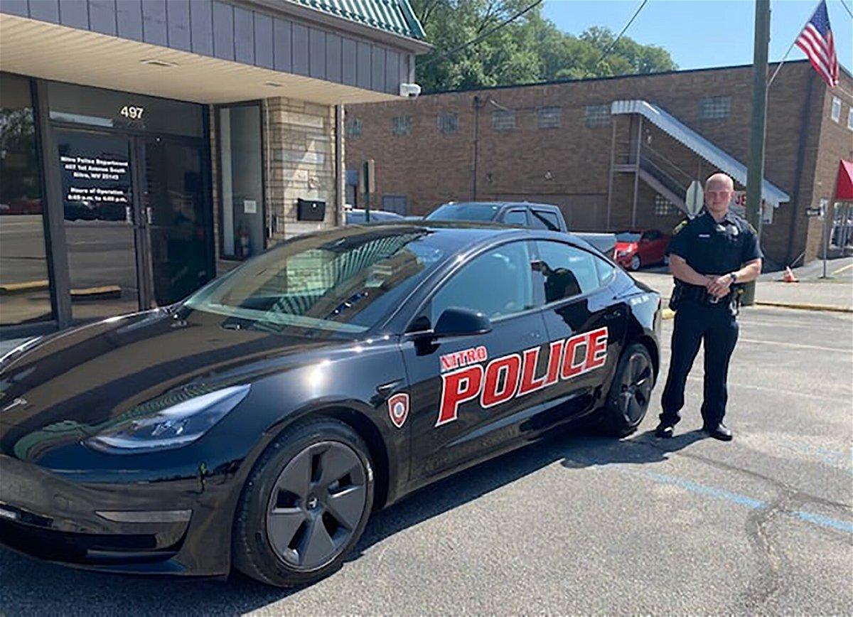 <i>Nitro Police Department/Facebook</i><br/>Patrolman Matt Haynes stands beside the new Tesla Model 3 electric patrol car.