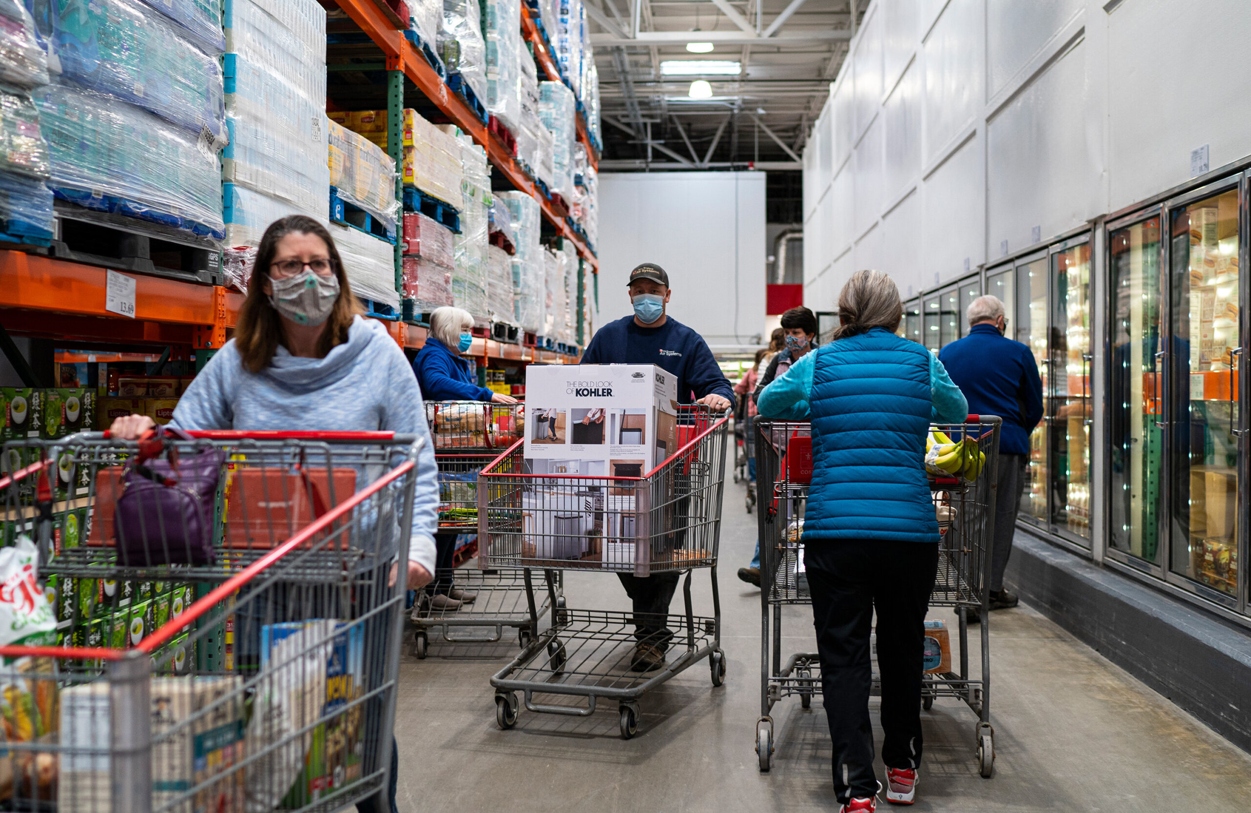 <i>Robert Nickelsberg/Getty Images</i><br/>Shoppers wearing masks search for items at a Costco Wholesale store on February 26 in Colchester
