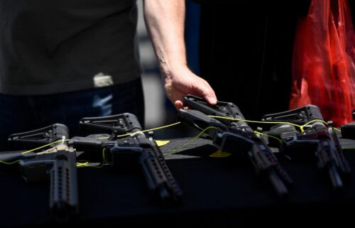 A customer examines a California-compliant AR-15 style rifle displayed for sale at a vendor booth at a gun show in Costa Mesa
