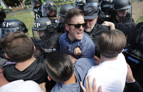 """White nationalist Richard Spencer (C) and his supporters clash with Virginia State Police in Emancipation Park after the """"Unite the Right"""" rally was declared an unlawful gathering on August 12"""