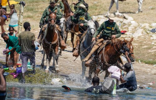 US Border Patrol agents on horseback try to stop Haitian migrants from entering an encampment on the banks of the Rio Grande near the Acuna Del Rio International Bridge in Del Rio